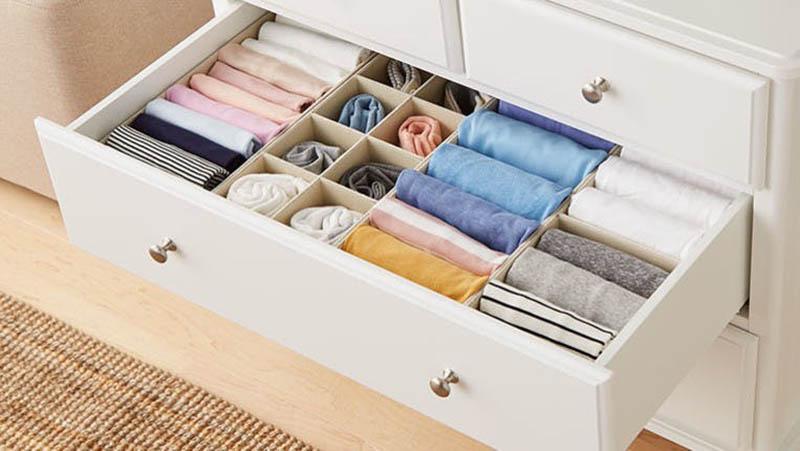 Cajón blanco con tiradores metálicos lleno de ropa doblada en vertical en compartimentos