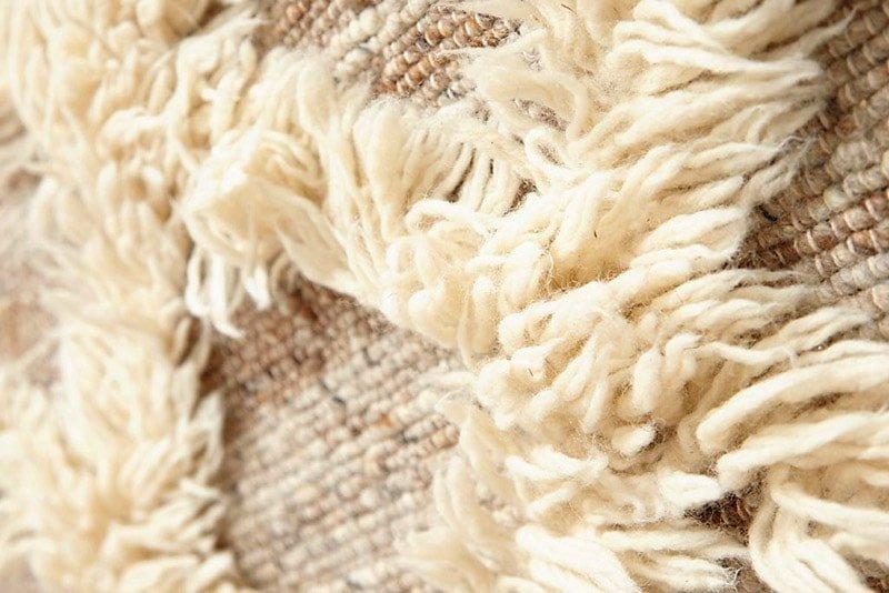 Detalle de alfombra de pelo largo de color natural y crudo