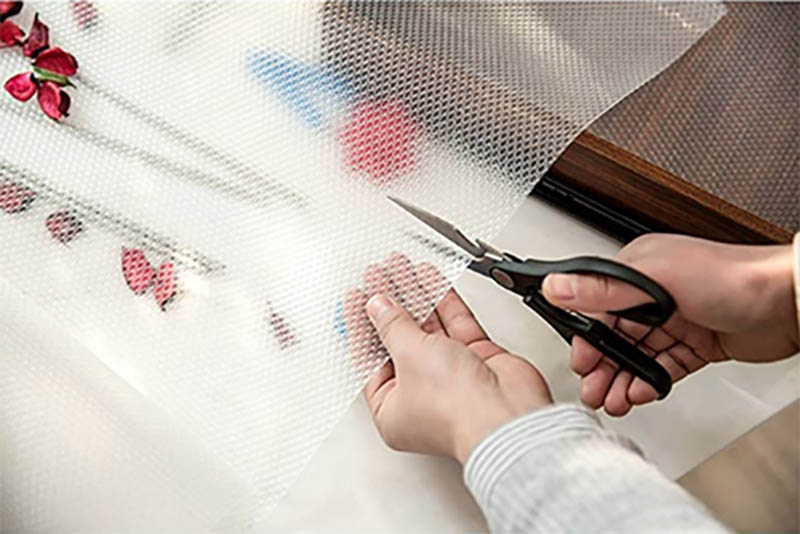 Una mano corta con tijeras negras una lámina de plástico antideslizante para los cajones