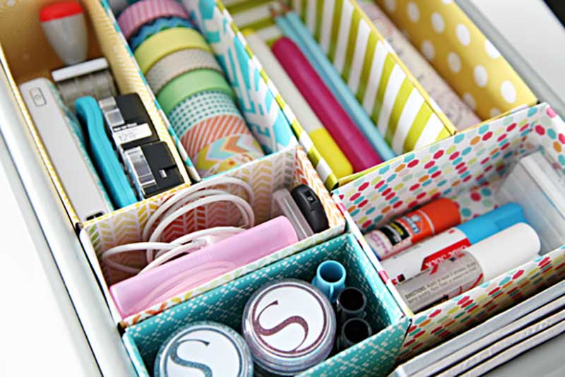 Cajón compartimentado con cajitas de colores lleno de material de papelería