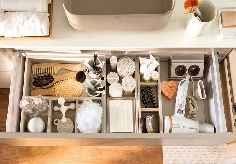 Cajón bajo el lavabo lleno de elementos e higiene y belleza