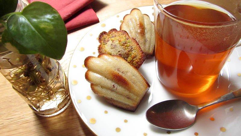 Un plato con madeleines con un té y una cuchara, en una encimera de madera con una planta y servilleta roja