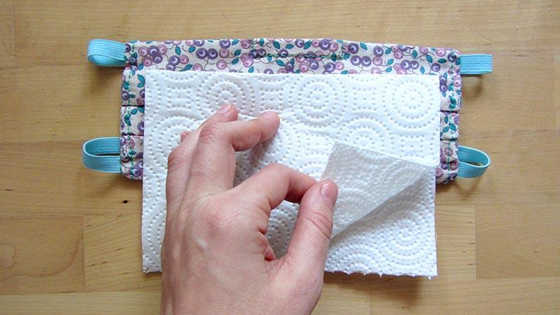 El filtro de papel de cocina de la mascarilla hecha en casa está recortada a medida encima de ésta