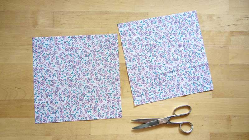 Unas tijeras y dos cuadrados de tela estampada iguales para hacer una mascarilla en casa