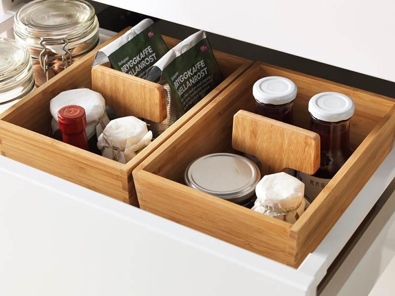 Cajón de cocina blanco con cestas de madera y productos de cocina dentro