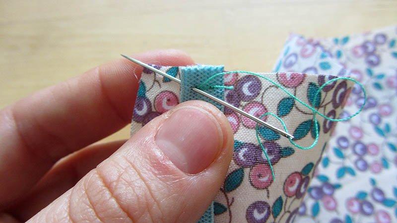 Detalle de cómo coser la goma a la tela en una mascarilla casera