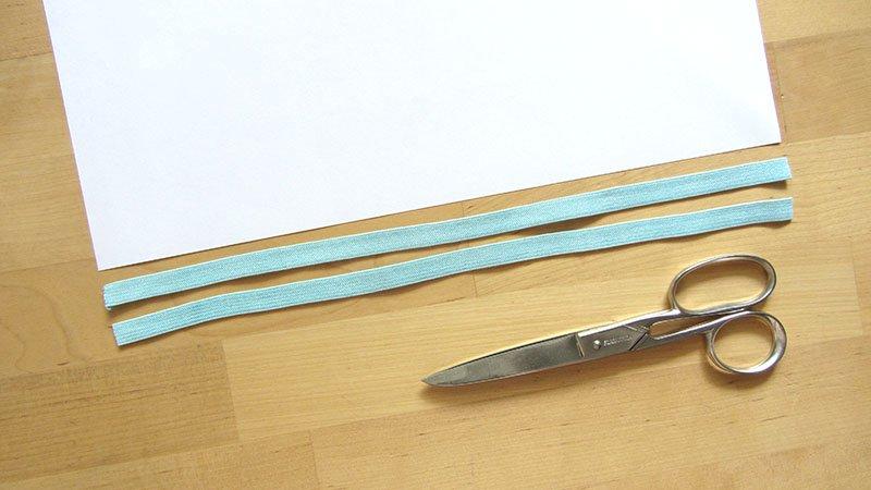 Un folio, dos gomas para hacer una mascarilla casera, cortadas a la medida del largo del papel y unas tijeras