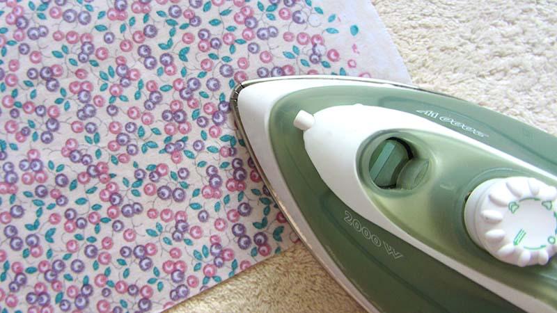Plancha sobre tela estampada planchando sobre una toalla beige