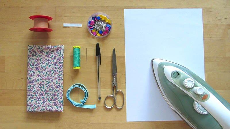Materiales necesarios para hacer mascarillas caseras sobre mesa de madera (tela, tijeras, hilo, aguja, alfileres etc)
