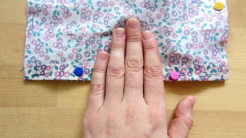 Sobre las telas de la mascarilla con alfileres, medimos tres partes con el ancho de los dedos