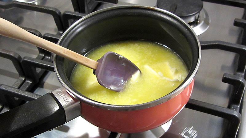 Derretir mantequilla en un cazo sobre una cocina de gas