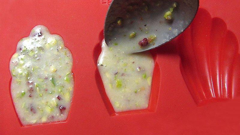 Detalle de una cuchara rellena con masa un molde de madeleines de almendra