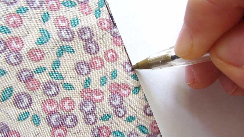 Un bolígrafo dibuja con plantilla sobre tela estampada para hacer una mascarilla casera