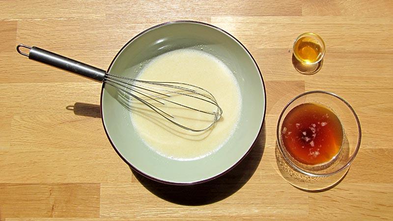 Mezcla ingredientes para hacer madeleines sin gluten en un cuenco con un batidor de varillas