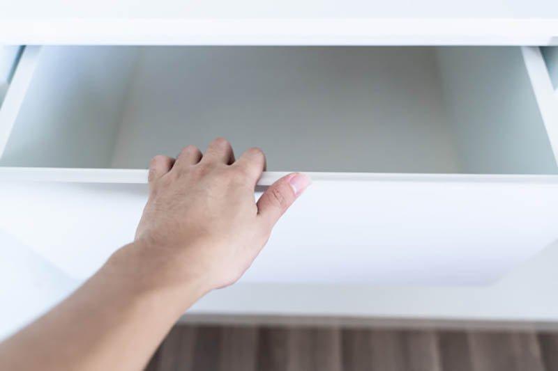 Una mano abre un cajón blanco vacío