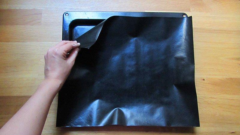 Una mano coloca una lámina antiadherente para hornear negra sobre una bandeja de horno