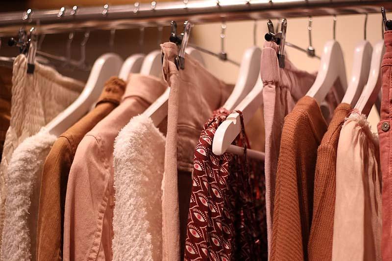 Ropa de entretiempo de tonos rosados colgada en perchas de una barra de armario