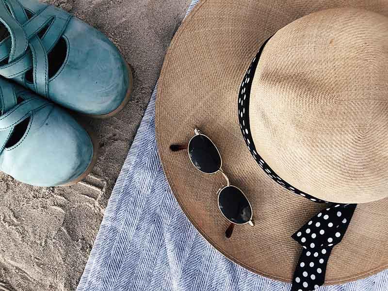 Un sombrero de paja, unos zuecos azules, unas gafas de sol y una toalla sobre arena de playa