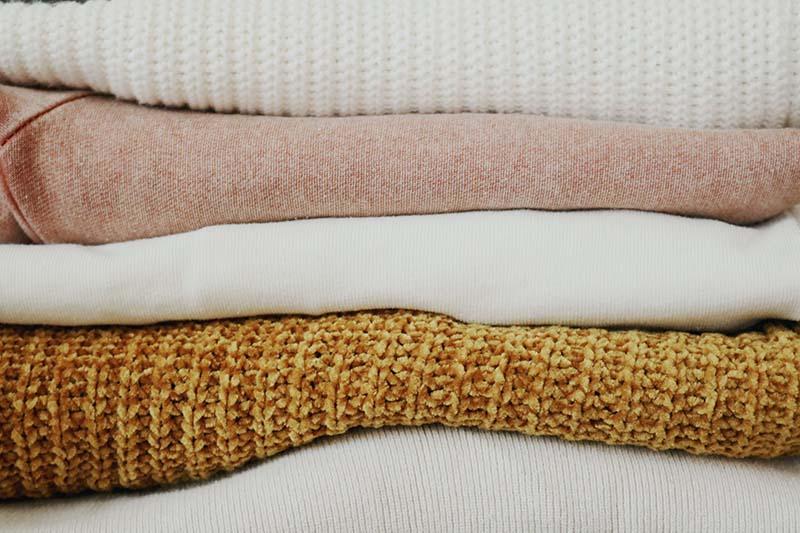 Detalle de varias prendas de invierno apiladas de colores blanco, mostaza y rosa