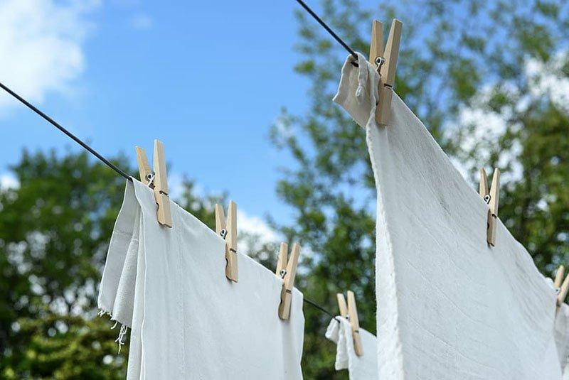 Dos paños blancos colgados con pinzas de un tendedero  al aire libre