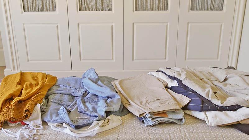 Montones de ropa seleccionada sobre la cama para organizar e armario ante la nueva temporada