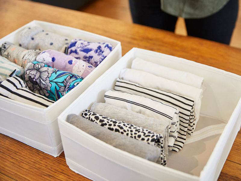 Ropa doblada en vertical estilo KonMari dentro de cajas de tela, para guardarlas en el cambio de armario