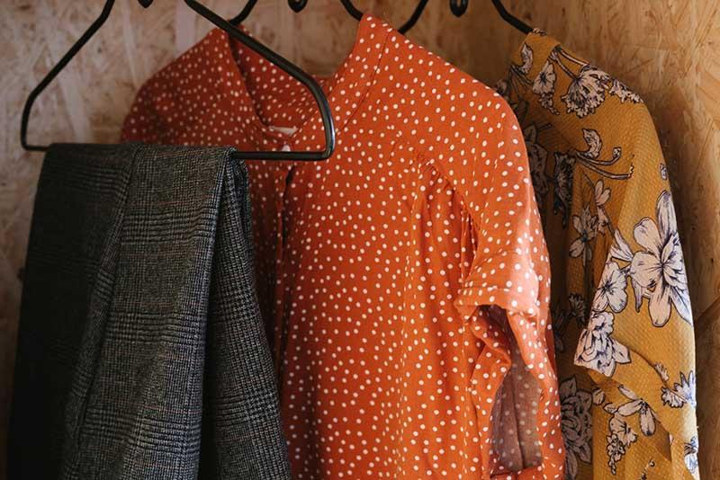 Ropa de verano de colores anaranjados colgadas de perchas dentro de un armario de madera