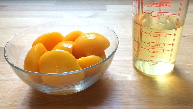 Unas mitades de melocotón en un cuenco, y medio litro de almíbar en una jarra de medición