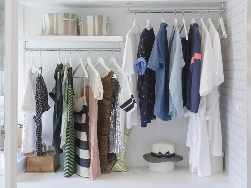 Armario muy ordenado con ropa de temporada colgada en perchas y algunos complementos