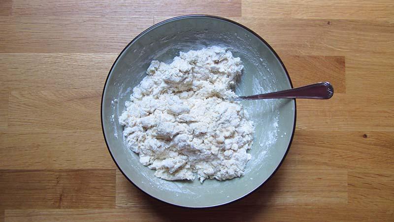 Masa de focaccia sin gluten mezclada con un tenedor dentro de un cuenco sobre una encimera de madera
