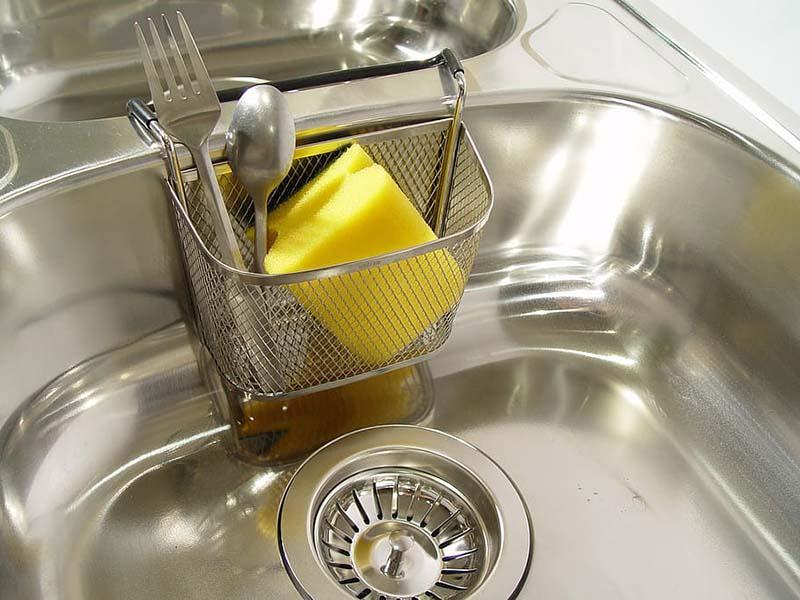 Fregadero limpio de acero inoxidable con cesta metálica y estropajo amarillo