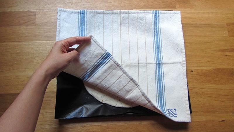 Una mano tapa una masa cruda con un paño de algodón sobre una bandeja de horno