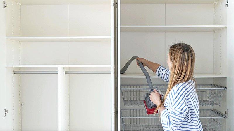 Una chica aspira un armario por dentro dejándolo listo para hacer el cambio de ropa de temporada