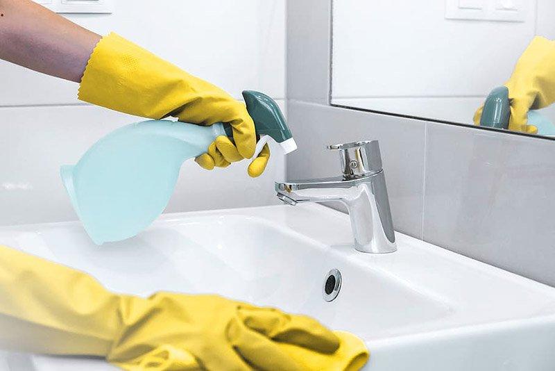 Unas manos con guantes amarillos limpian un lavabo y un grifo de acero