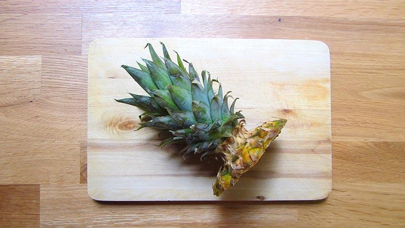 Penacho de hojas de piña cortado sobre una tabla de madera