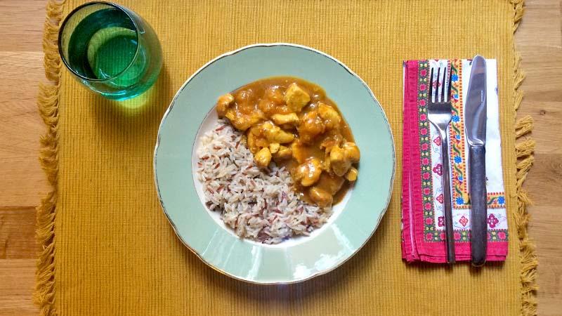 Un mantel individual con vaso, cubiertos y un plato de curry de pollo con cebolla y melocotón