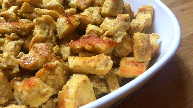 Detalle de trocitos de pechuga de pollo especiada y dorada en un plato