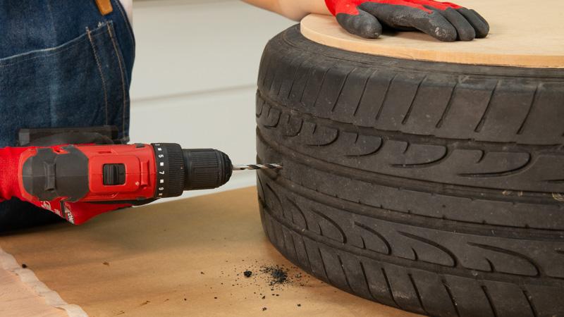 Taladro abriendo un agujero en el neumático para poder fijar las asas de cuero del asiento casero