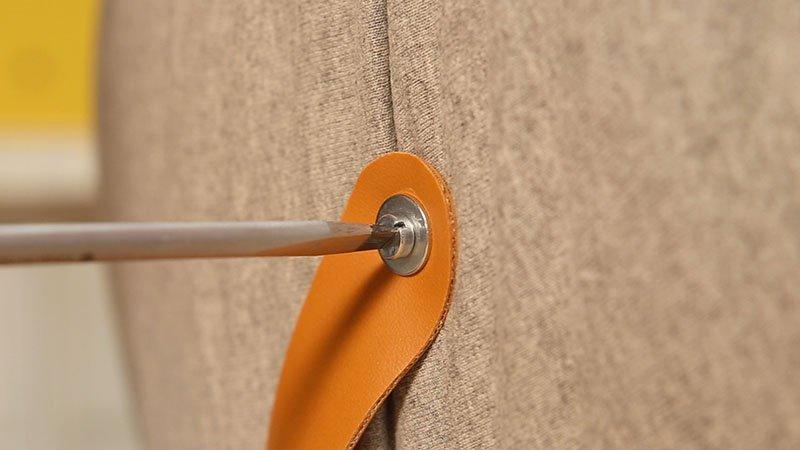 Fijación de un asa de cuero en el puff casero mediante un tornillo