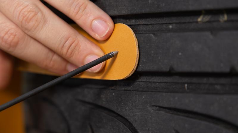 Punzón abriendo un agujero en una tira de cuero para fijarla al neumático