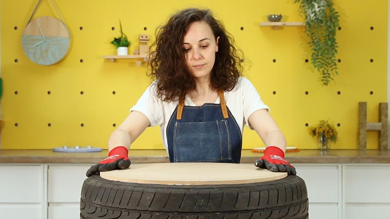 Pegado de una pieza circular de madera sobre un neumático para hacer un asiento