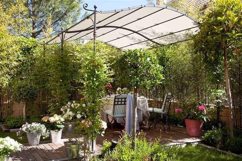 Jardín pequeño frondoso con una pérgola metálica y una mesa con sillas