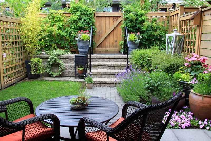 Jardín con muebles oscuros, escaleritas de piedra y diferentes materiales como madera, piedra y vegetación