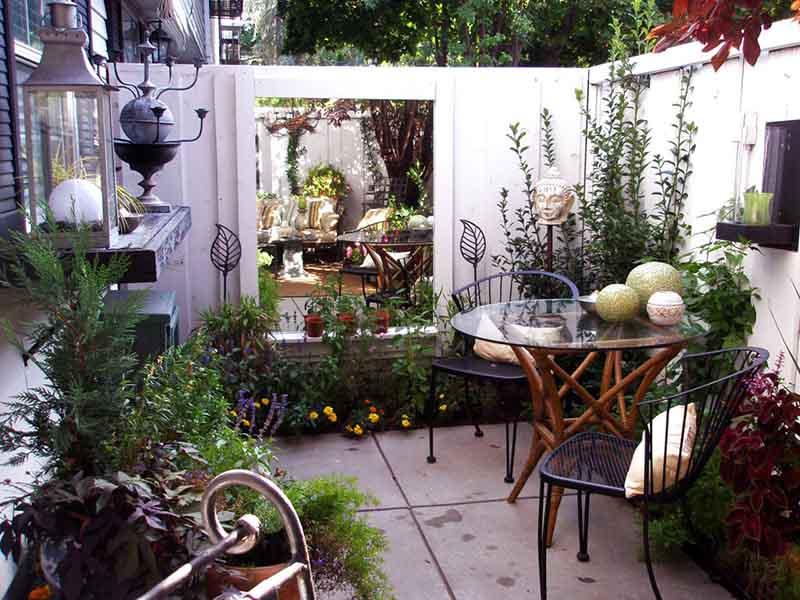 Rincón de un patio reducido con paredes blancas, muebles metálicos y un espejo reflejando las plantas