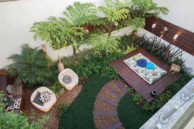 Vista cenital de un patio con plantas, un camino curvo, césped y una tarima de madera