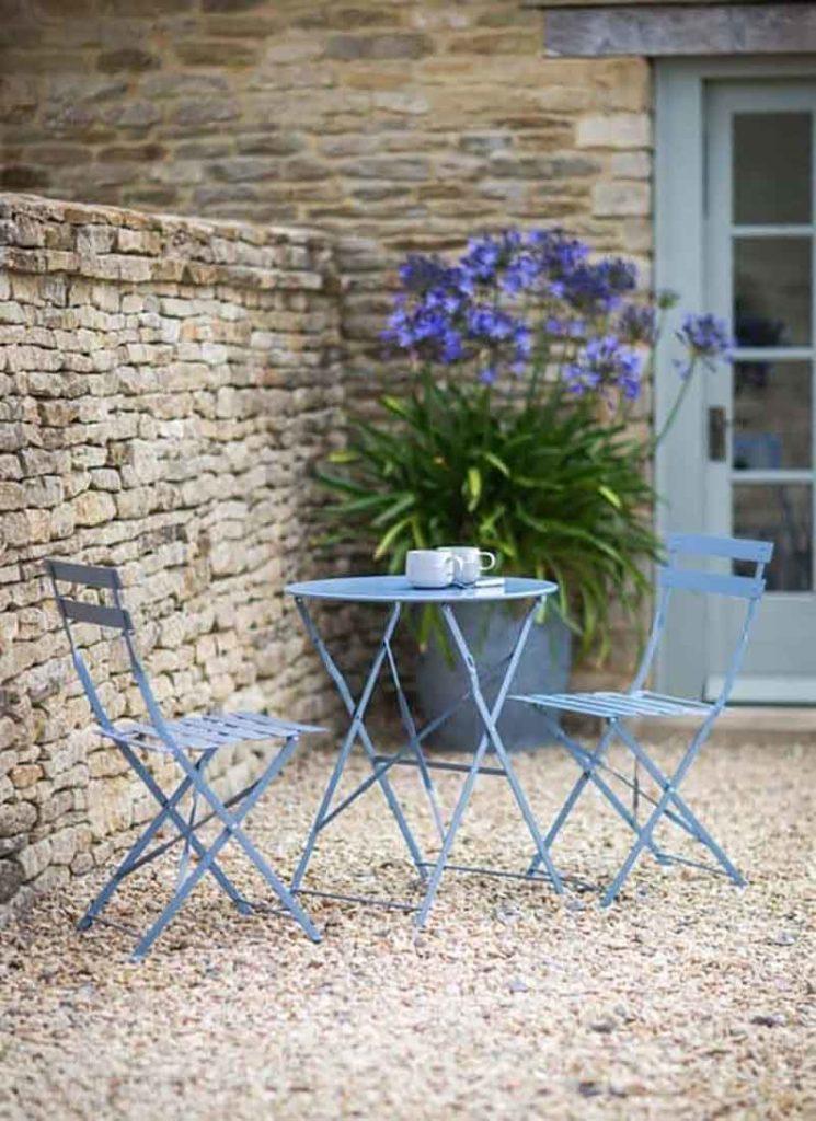 Dos sillas y una mesa metálicas azules en un jardín de piedra junto a un muro