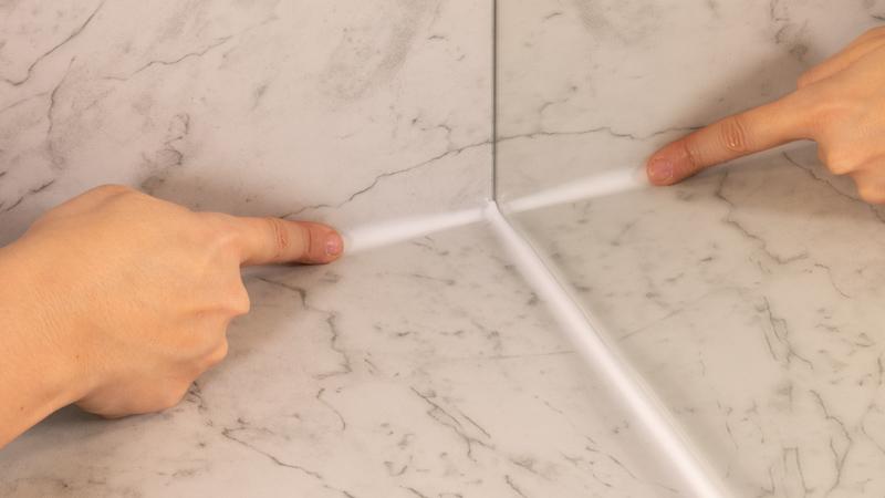 Dedo alisando una junta de silicona en un espejo