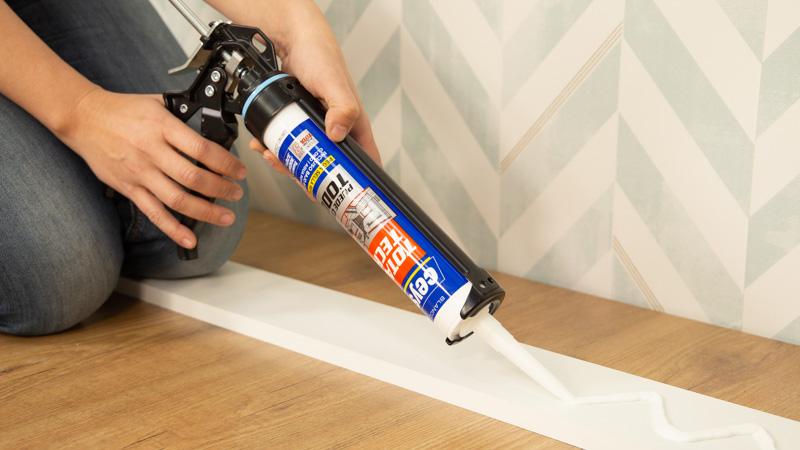 Aplicación de un adhesivo sellador sobre un rodapié de madera