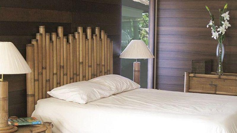 Cabecero de cama hecho con cañas gruesas de bambú