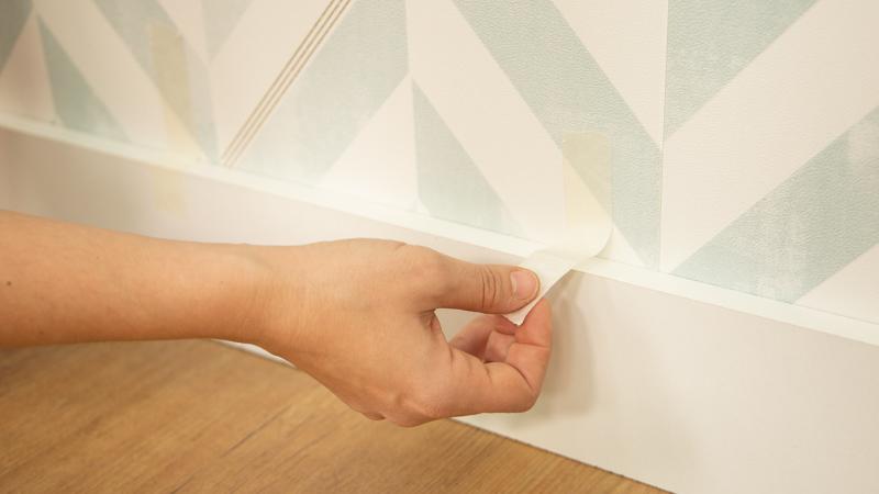 Colocación de cinta de carrocero para dejar secar el adhesivo de un rodapié recién colocado